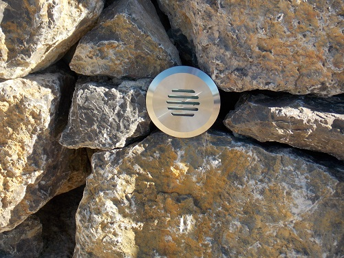 Louvre 316 stainless steel light in stone wall